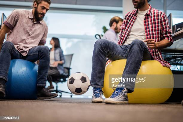 playing with soccer ball on a break in the office! - fitness ball stock pictures, royalty-free photos & images