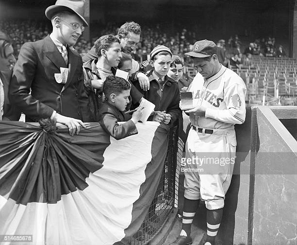 Playing with the Boston Braves, Babe Ruth signs autographs for fans at the New York Giants' home opener against the Braves at the Polo Grounds. New...