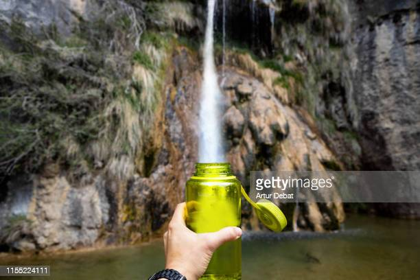 playing with the perspective filling bottle of water from waterfall. - soggettiva foto e immagini stock