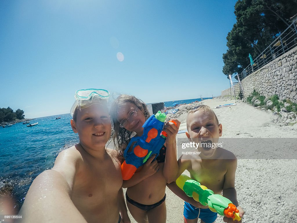 Two boys and one girl are playing with water guns at the sea. They spray water at the camera.
