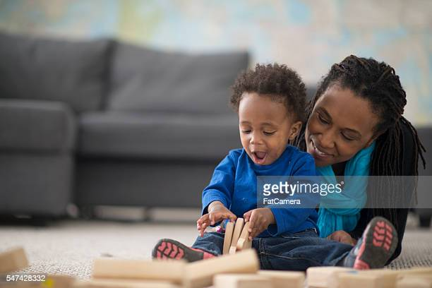 playing with wooden blocks - african american family home stock photos and pictures