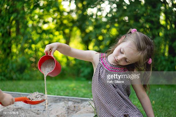 playinjg girl - 2 kid in a sandbox stock photos and pictures