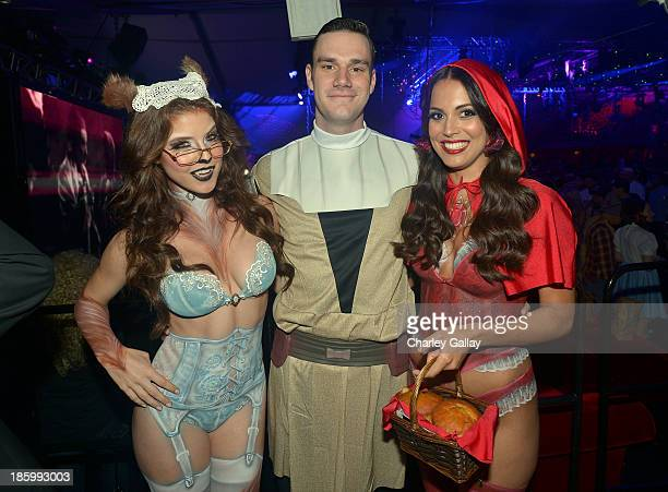 Playmate Amanda Cerny, Cooper Hefner and Playmate of the Year Raquel Pomplun attend Playboy Mansion's annual Halloween bash on October 26, 2013 in...