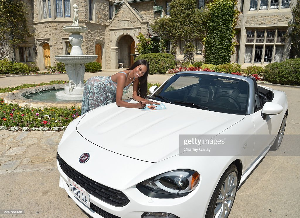 Playmate of the Year Eugena Washington signs a copy of her Playboy issue on her new All-New 2017 Fiat 124 Spider at Playboy's 2016 Playmate of the Year Announcement at the Playboy Mansion on May 11, 2016 in Los Angeles, California.