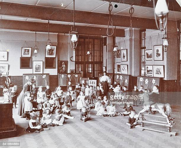Playtime John Ruskin School Southwark London 1908 Young children playing with toys in the school hall One boy is riding a splendid rocking horse...