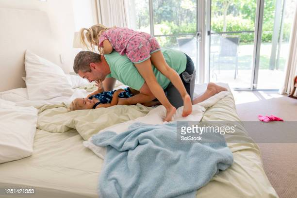 playtime with family - child in bed clothed stock pictures, royalty-free photos & images