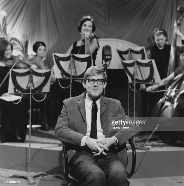 Playwright Alan Bennett in front of an orchestra 1964