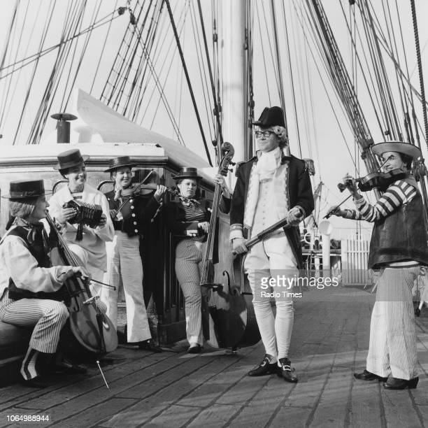 Playwright Alan Bennett on the deck of a ship wearing an old fashioned Naval officers uniform 1964