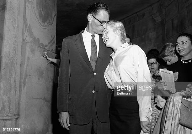 Playwright Arthur Miller kisses his fiancee, Marilyn Monroe, outside her Manhattan apartment. They met the press for the first time since their...
