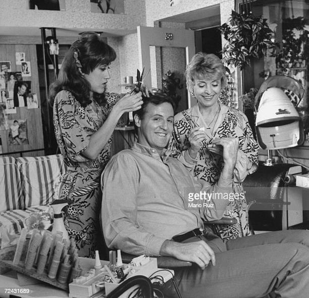 Playwright Robert Harling posing in beauty parlor chair on the stage set with cast members Constance Shulman Rosemary Prinz dressed for their...