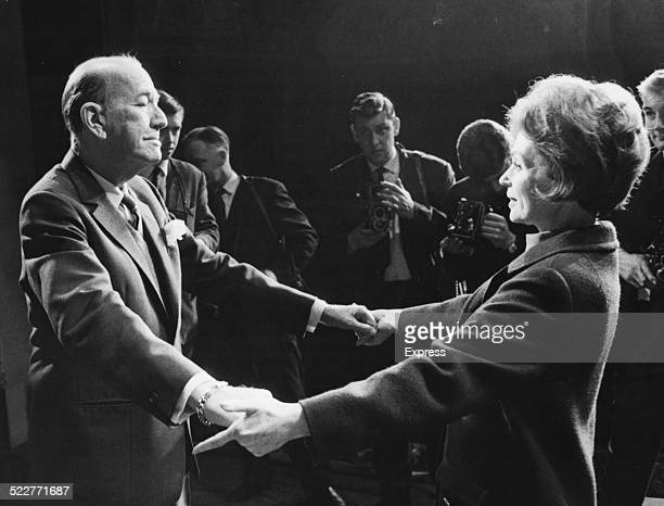 Playwright Sir Noel Coward greeting actress Lilli Palmer with open arms surrounded by press photographers on stage at the Queen's Theatre London...