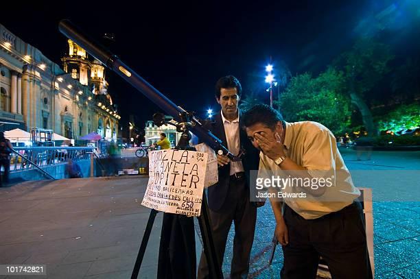 An astronomer teachers a tourist about Jupiter through a telescope.