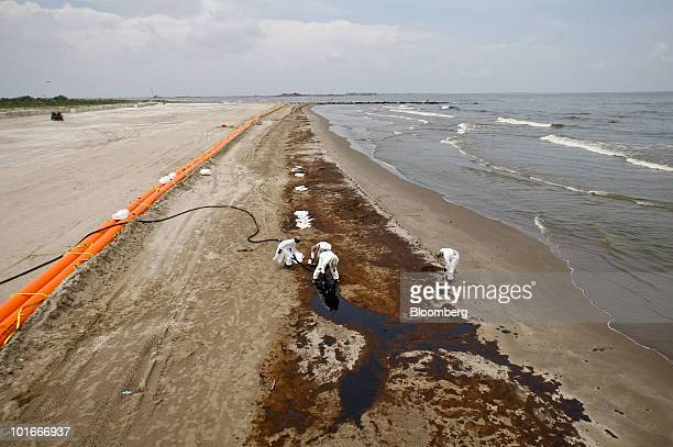 BP Plc contract workers remove oil that washed onto the beach at Grand Isle State Park in Grand Isle Louisiana US on Sunday June 6 2010 A Tiger Dam...
