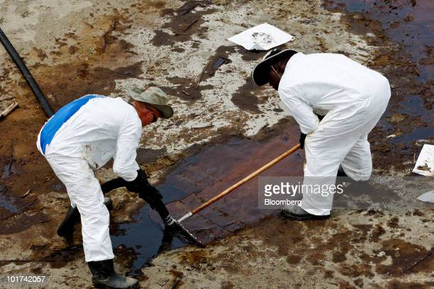 BP Plc contract workers use a vacuum hose to clean oil from the beach at Grand Isle State Park in Grand Isle Louisiana US on Sunday June 6 2010 The...
