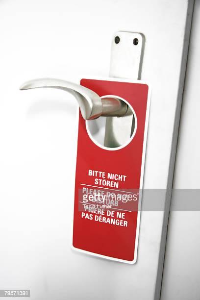 'Please do not disturb sign on door handle, close-up'