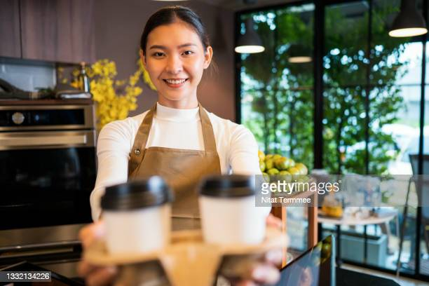 please enjoy drinking a coffee. the part-time waitress serving coffee to a customer in a cafe. serving food and drink, point of sale system, and part-time jobs. - coffee drink stock pictures, royalty-free photos & images
