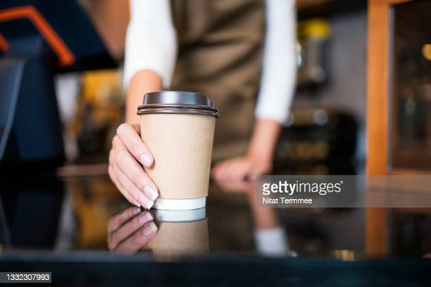 please enjoy drinking a coffee. the unrecognizable waitress serving coffee to a customer in a cafe. serving food and drink, point of sale system. - coffee drink stock pictures, royalty-free photos & images
