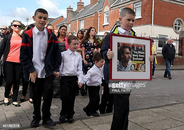 Please Note additional information added to caption Padraig McKernan aged 10 great nephew of Gerry Conlon carries a framed newspaper headline behind...