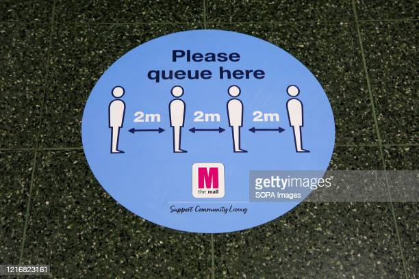 Please queue here sticker seen on the floor at a shopping mall in north London
