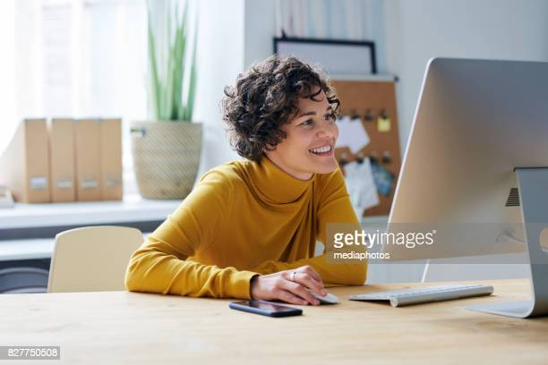 pleased business lady in front of computer - using computer stock photos and pictures