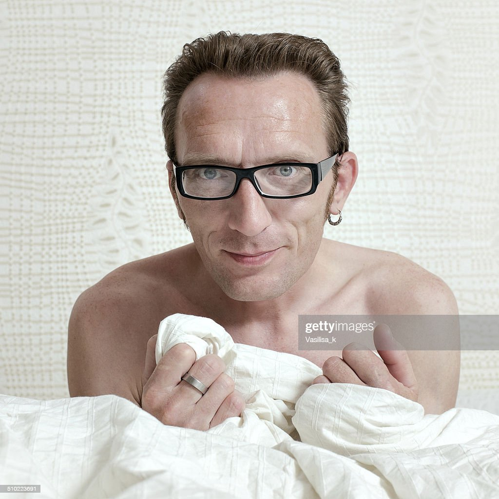 Pleased Handsome Naked Man In Bed Under The White Quilt Stock Photo