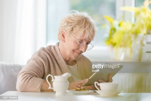 pleased senior woman using digital tablet - medical condition stock pictures, royalty-free photos & images
