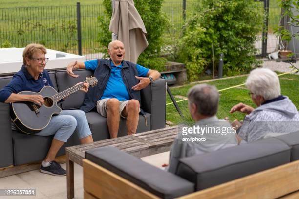 喜ぶ高齢者が歌い、庭で屋外で一緒に音楽を作る - オープニングイベント ストックフォトと画像