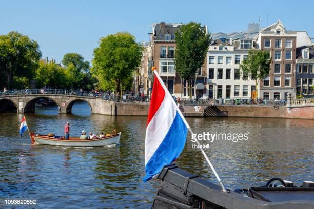 pleziervaartuig en nederlandse vlag op de amsterdamse gracht - nederlandse vlag stockfoto's en -beelden