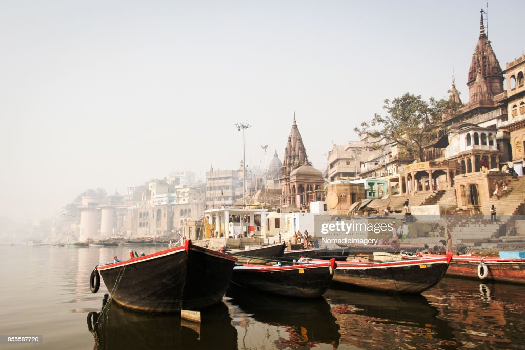 Pleasure boats and ancient Hindu temples on River Ganges : Stock Photo