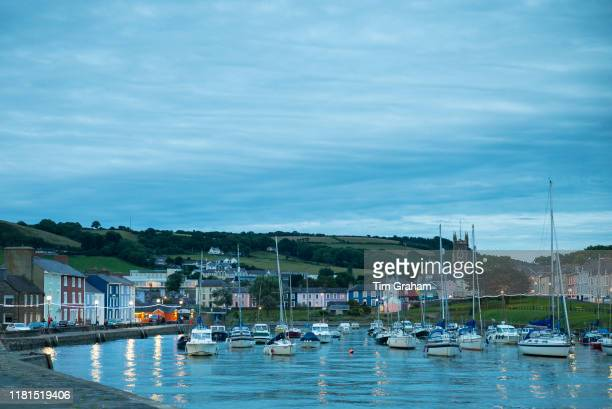 Pleasure boats powerboats and yachts in harbour seaside housing at sundown / dusk in Aberaeron Pembrokeshire Wales United Kingdom