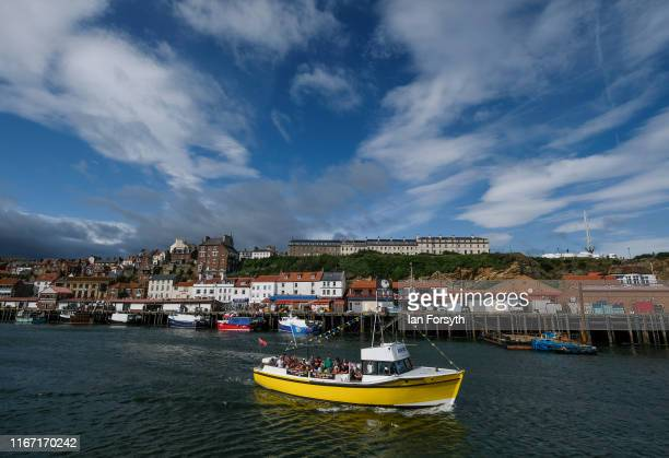 A pleasure cruiser carries passengers on a sight seeing tour out of Whitby harbour during the annual Whitby Regatta on August 10 2019 in Whitby...