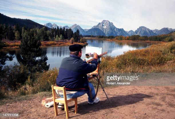 A plein air artist paints Mt Moran and the Teton Range in the distance in Grand Teton National Park in Wyoming 5104602RA_Teton09