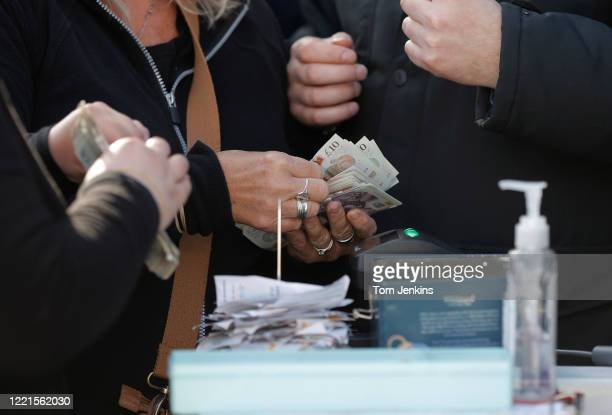 Plenty of cash being handled by a bookmaker with a bottle of hand sanitizer nearby during day four of the Cheltenham National Hunt Racing Festival at...