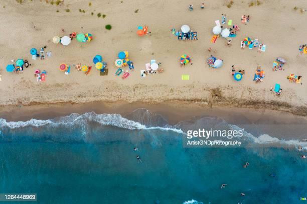 beaucoup de gens méconnaissables à la plage, vibes tropicales et vacances - marque de bronzage photos et images de collection