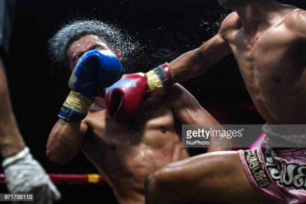 Plerngarom punches Pongsin a Thai boxing combat in 54kg category during Muaythai Monday Evening International Thai Boxing Gala in Thaphae Stadium in...