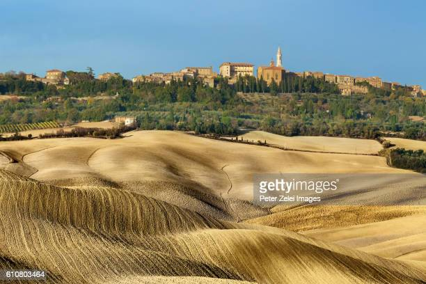 Ploughed fields in Tuscany with the small town of Pienza in the background, Italy