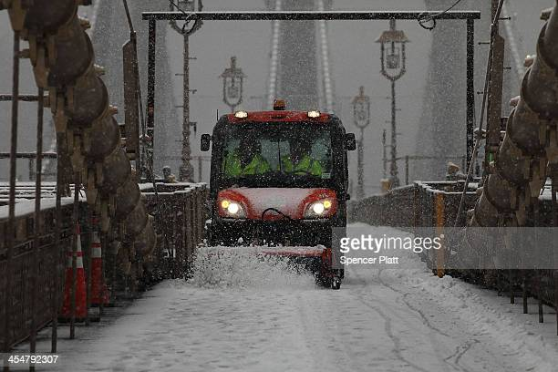 A plow clears the pedestrian walkway on the Brooklyn Bridge during the season's first snow storm on December 10 2013 in New York City As snow is...