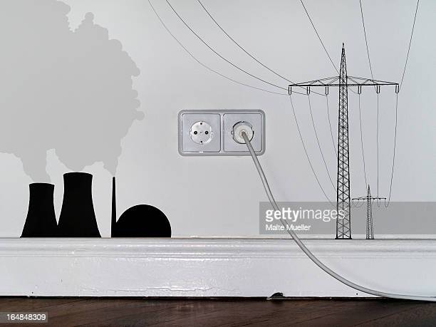 A plug in an outlet in between decals of a nuclear power station and electricity pylons