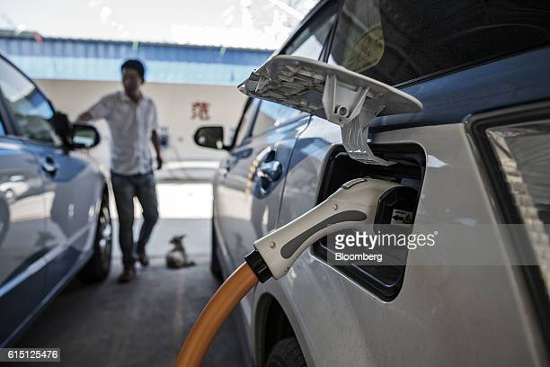 A plug is connected to the socket of a BYD Co E6 electric taxi being charged at a charging station in Taiyuan Shanxi province China on Tuesday Sept...