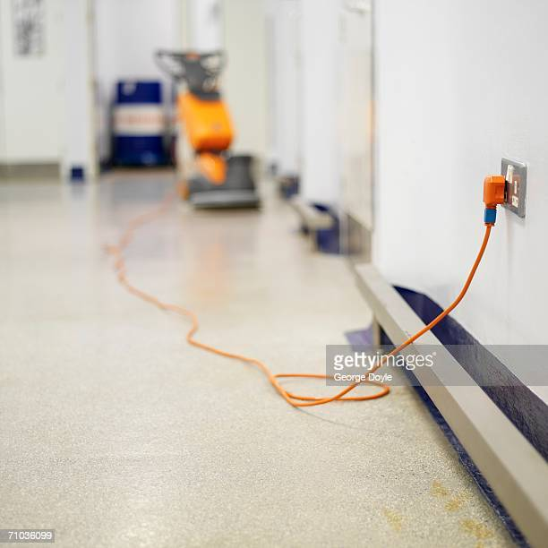 Plug of a floor polisher plugged into the wall