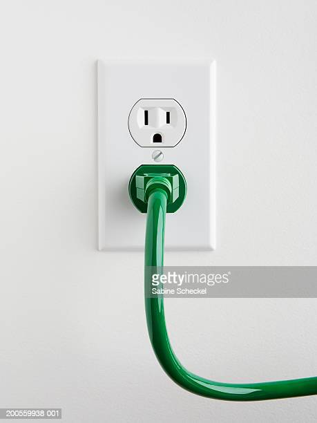Plug socket with green power cable on wall, close-up