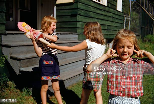 Plugging Ears as Girls Fight over Doll