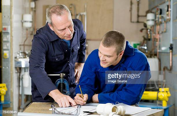 plumber and apprentice - brilliant stock photos and pictures