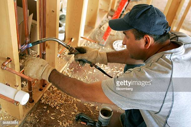 Plumber Andrey Sumilovas uses a blow-torch to seal copper pipes in a new home under construction in Park Ridge, Illinois, U.S., on Tuesday, June 24,...