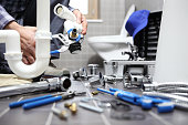 plumber at work in a bathroom, plumbing repair service, assemble and install concept