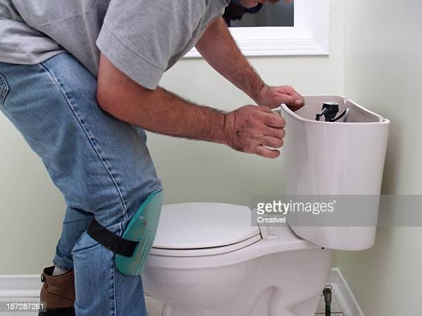 Plumber at work repearing toilet