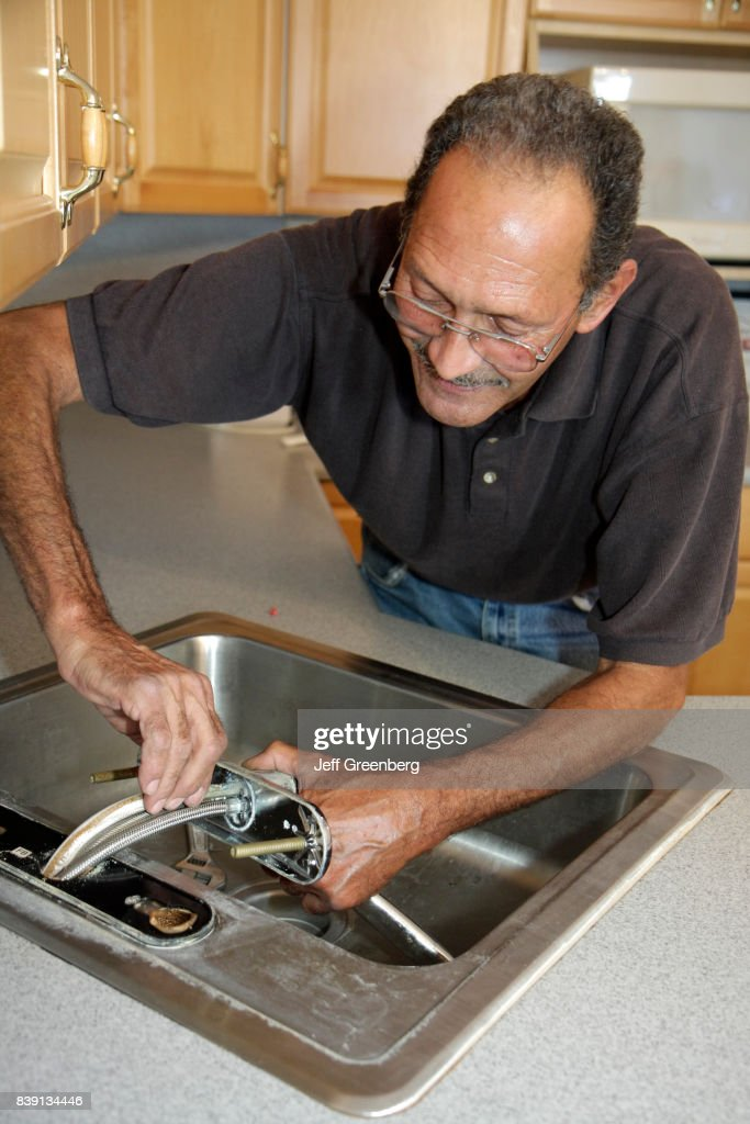 A plumber fixing a kitchen sink in a condominium apartment at ...
