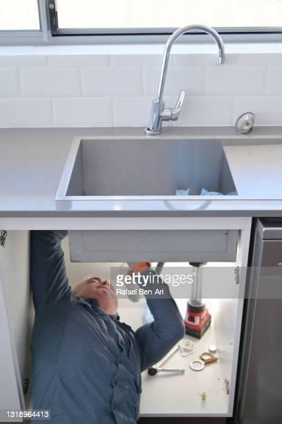 plumber fixing and repairing a kitchen faucet tap leaking - rafael ben ari photos et images de collection