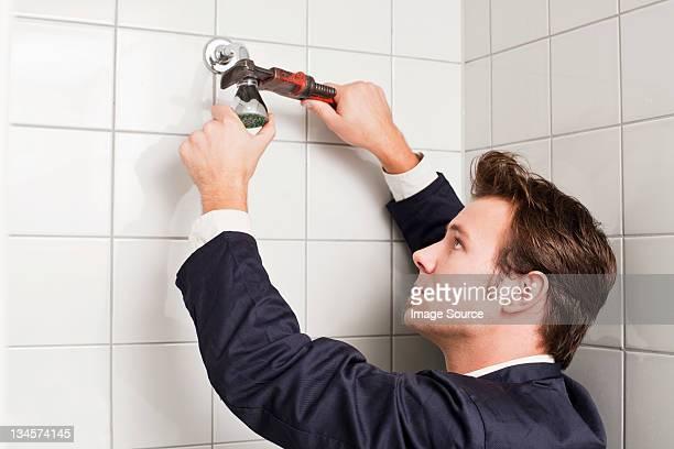 Plumber fixing shower head