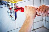 Plumber hands holding wrench and fixing a sink in bathroom